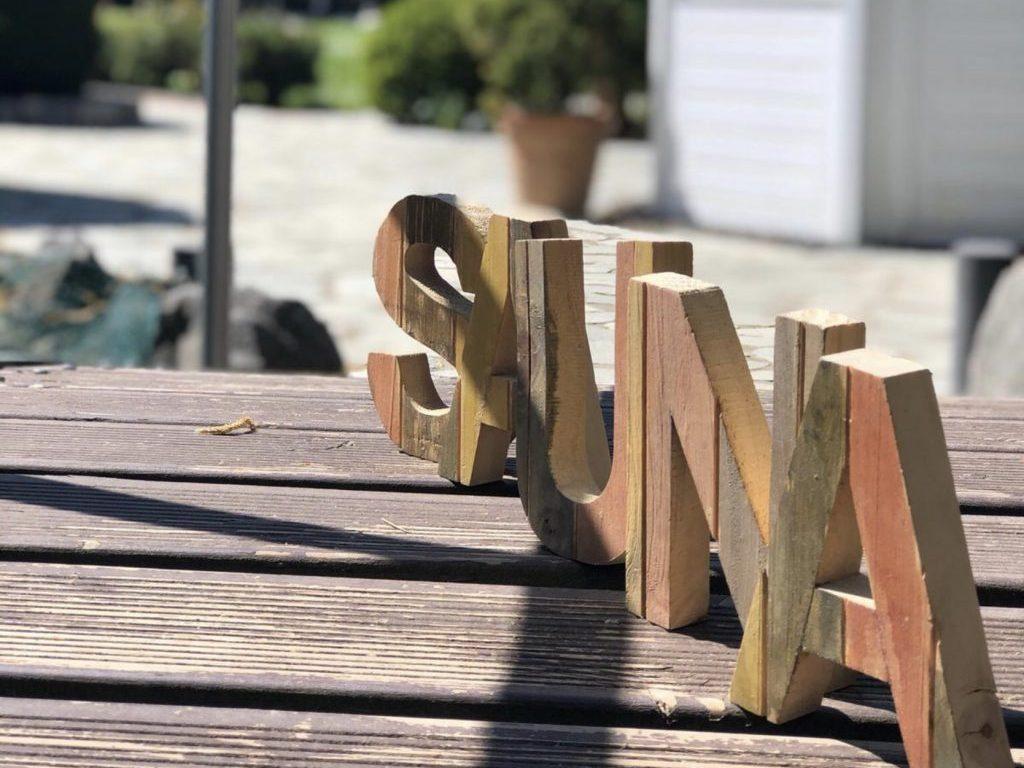 Foto vom Wort Sauna in Holzbuchstaben auf Holztisch